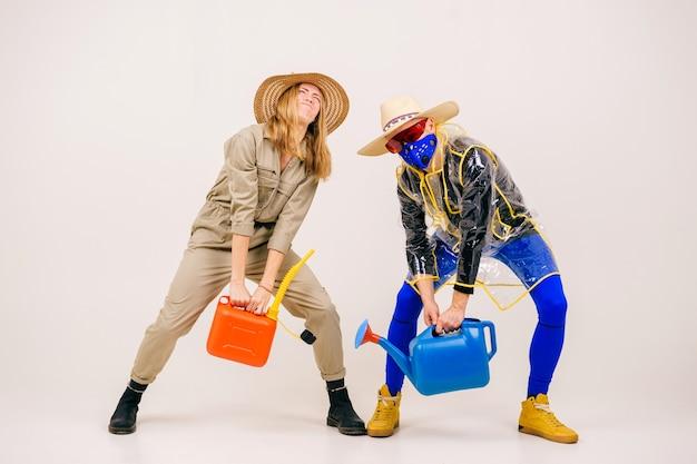 Uomo alla moda con la maschera e la donna in cappelli di paglia in posa con annaffiatoio sul muro bianco