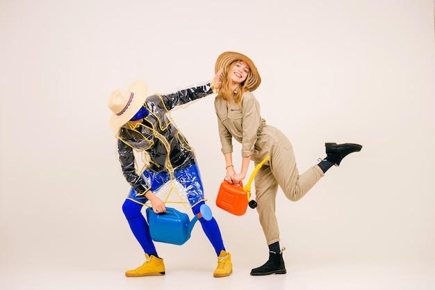 Uomo alla moda con la maschera e la donna in cappelli di paglia in posa con annaffiatoio