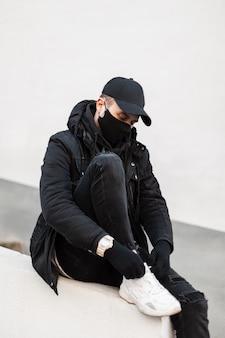 Elegante modello da uomo con maschera medica e berretto in look urbano alla moda con giacca. felpa con cappuccio e scarpe da ginnastica si siede e si allaccia i lacci delle scarpe per strada