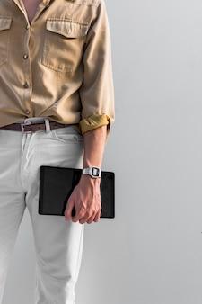 Uomo alla moda in posa all'aperto tenendo tablet