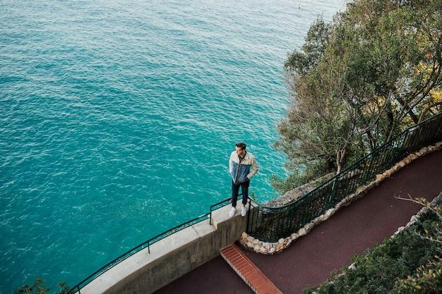Elegante uomo in piedi di fronte a un vasto mare calmo con limpide acque azzurre ammirando incredibile vista marina.