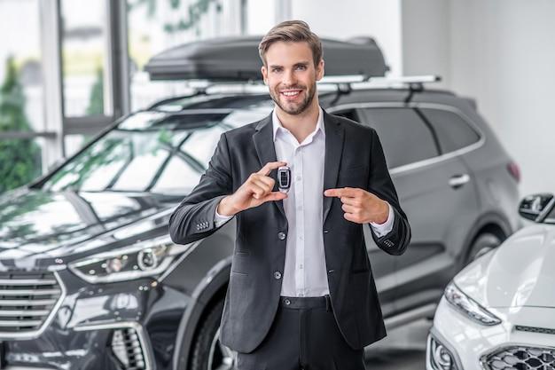 Uomo alla moda in vestito allo showroom di automobili