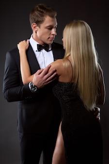 Un uomo elegante in completo e una ragazza in abito nero da sera si abbracciano teneramente guardandosi negli occhi