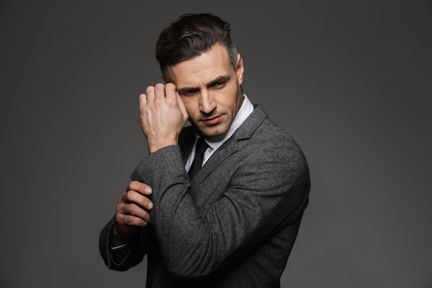 Abito da portare dell'uomo alla moda che osserva da parte, mentre fissi il gemello o il bottone sulla manica della giacca, isolata sopra la parete grigia