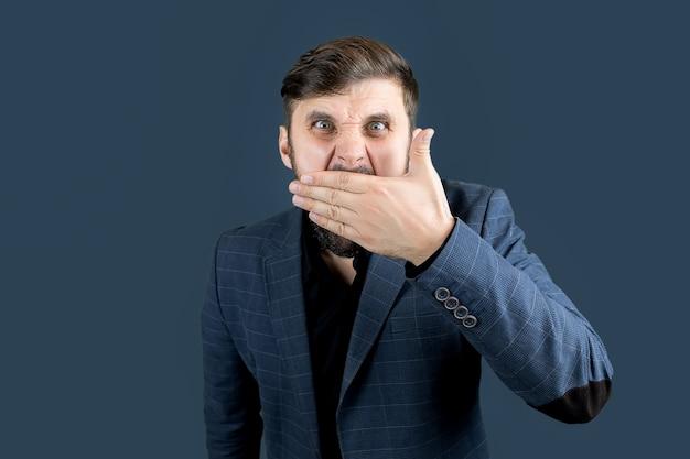 Un uomo elegante con la barba in abito blu si coprì la bocca con la mano
