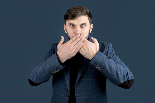 Un uomo elegante con la barba in abito blu si coprì la bocca con due mani