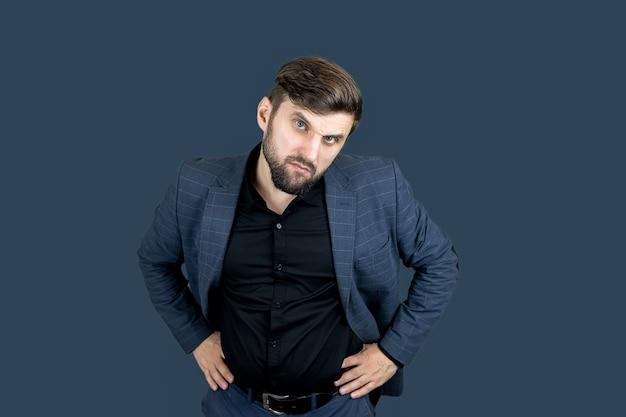 Un uomo elegante con la barba in abito blu tiene le mani sulla cintura e guarda la telecamera