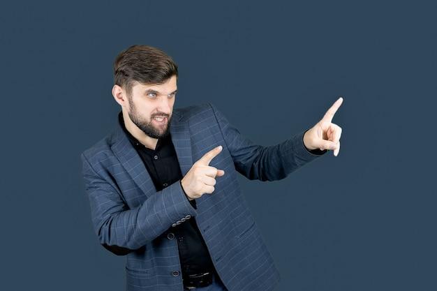 Un uomo elegante con la barba in abito blu mostra la direzione con entrambe le mani