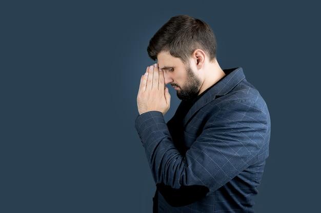 Un uomo elegante con la barba in abito blu sta di lato e tiene le mani davanti al viso