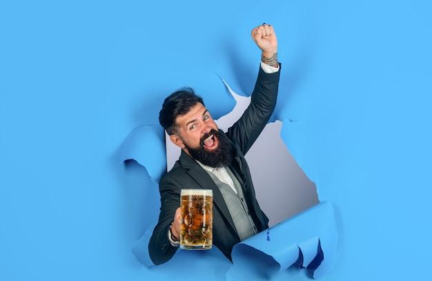 Uomo alla moda con barba tenere boccale di birra. oktoberfest. lager e birra scura. l'uomo barbuto tiene la birra artigianale guardando attraverso il foro della carta. bevande, alcol, tempo libero, concetto di persone. uomo barbuto che beve birra.