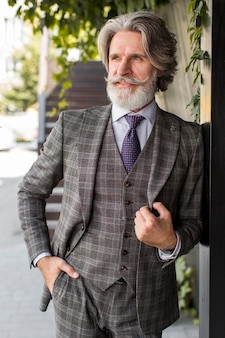 Uomo alla moda con la barba che propone all'aperto