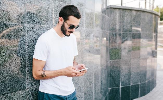Uomo alla moda con il tatuaggio e la barba con gli occhiali e una maglietta bianca utilizza il suo smartphone