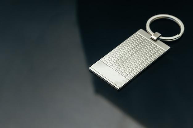 Elegante ciondolo chiave in metallo maschile su vetro nero da vicino