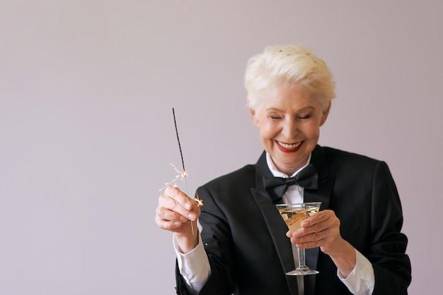 Elegante donna anziana matura che celebra il nuovo anno
