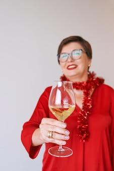 Elegante donna anziana matura in camicetta rossa con un bicchiere di vino bianco per celebrare il nuovo anno
