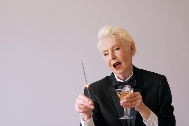 Elegante donna anziana matura in smoking per celebrare il nuovo anno