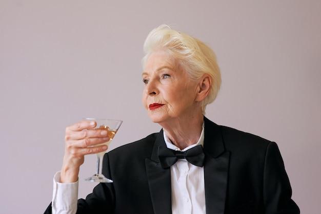Elegante matura sommelier donna anziana in smoking con un bicchiere di spumante