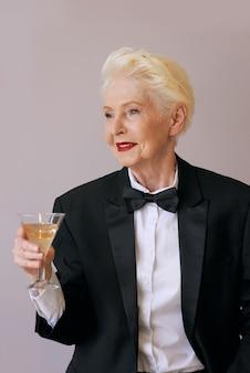Elegante matura sommelier senior donna in smoking con un bicchiere di spumante
