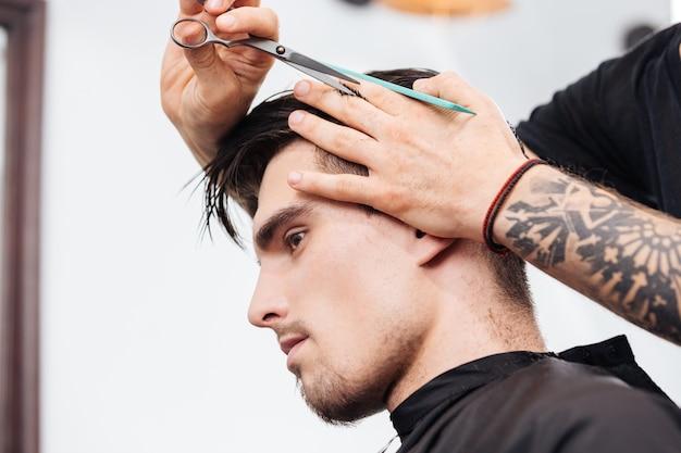 Acconciatura e taglio di capelli da uomo alla moda in un barbiere o in un parrucchiere