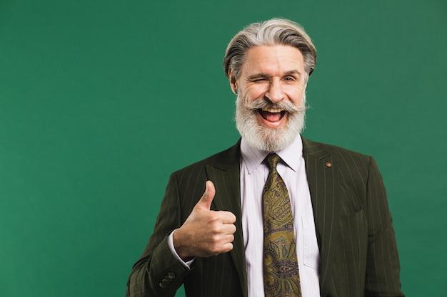 Elegante uomo di mezza età con la barba in tuta mostra il pollice sul muro verde