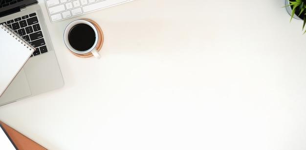 Elegante postazione di lavoro minimalista con tastiera, laptop, forniture per ufficio in stile piatto laici