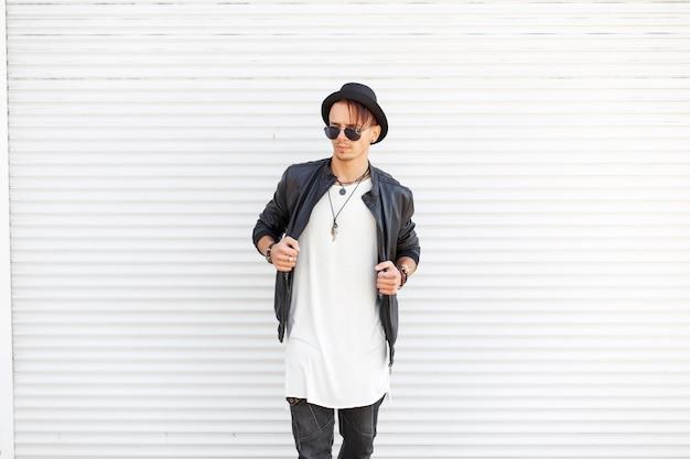 Uomo modello elegante in un cappello alla moda con occhiali da sole in una giacca nera alla moda e una t-shirt bianca vicino a porte di metallo