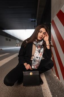 Elegante modello giovane donna in abbigliamento alla moda con sciarpa vintage in stivali con borsa in pelle nera alla moda è rilassa nel parcheggio vicino al pilastro a strisce. elegante ragazza di moda in posa in città.