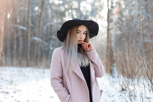Elegante e moderna bella giovane donna in un abito vintage lavorato a maglia in un elegante cappello nero in un elegante cappotto rosa in posa nel bosco