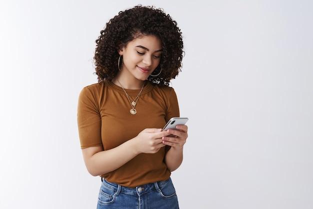 Elegante ragazza moderna che controlla la cassetta postale tenendo lo smartphone guarda lo schermo del telefono sorride felice messaggistica scrivendo post social media scorrimento pagina feed app in piedi sfondo bianco