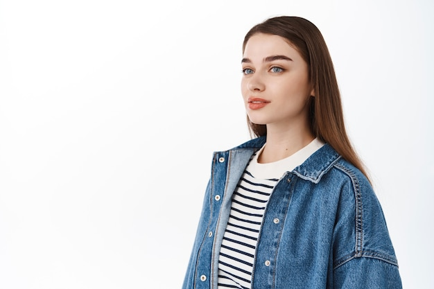 Elegante ragazza moderna in piedi mezzo girata e guardando da parte, in posa vicino allo spazio della copia, posto bianco vuoto per pubblicità o testo promozionale, in piedi al muro dello studio