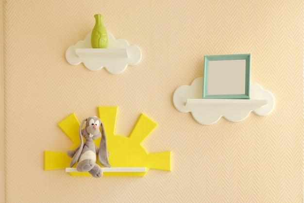Design degli interni elegante e moderno. casa per la stanza dei bambini. scaffali per bambini a forma di nuvole bianche su una semplice parete beige con una cornice per foto e una lepre grigia e un vaso.
