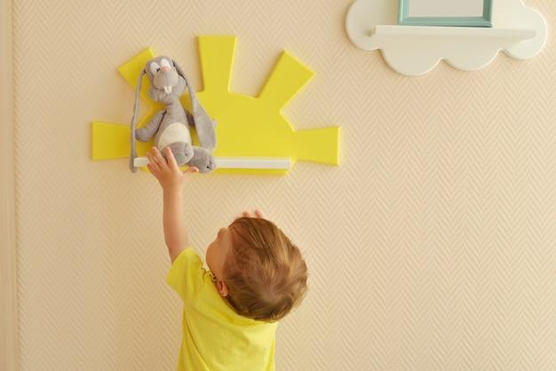 Design degli interni elegante e moderno. casa per la stanza dei bambini. bambino più piccolo prende il peluche di una lepre grigia dallo scaffale.