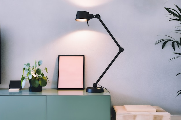 Interni moderni ed eleganti, cornice vuota con lampada nera e pianta verde dei soldi cinesi, pianta dei pancake retrò sul design scandinavo del tavolo verde