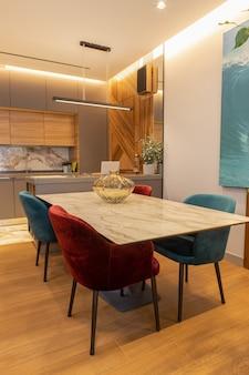 Interno moderno ed elegante della cucina, studio grande tavolo con sedie in velluto. zona soggiorno, sala da pranzo, pannello di design in legno impiallacciato a parete. concept minimal interni alla moda, materiali naturali.