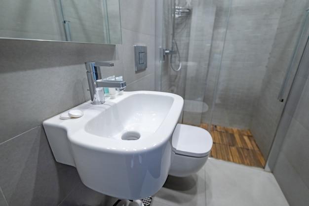 Lavandino bianco moderno alla moda della nave sotto lo specchio e il rubinetto di acqua nell'interno domestico del bagno. bagno con doccia nell'appartamento