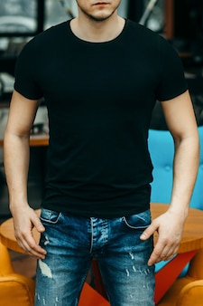 Uomini muscolosi alla moda che indossano maglietta nera in posa in studio