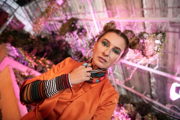 Servizio fotografico alla moda. piacevole bella donna che si tocca il collo mentre posa