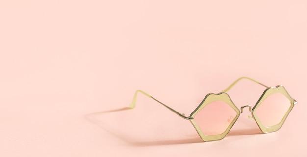 Occhiali da sole rosa alla moda a forma di labbra su sfondo rosa con copia spazio