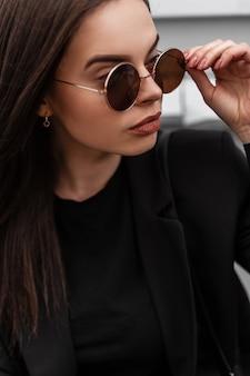 Elegante ritratto bella giovane donna con labbra sexy con pelle pulita sana in blazer alla moda in occhiali rotondi vintage vicino a edificio in legno in città. la ragazza urbana raddrizza gli occhiali da sole alla moda.