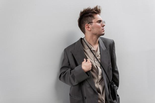 Ritratto alla moda di un bell'uomo d'affari con una giacca e una camicia alla moda su uno sfondo grigio