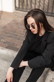 Elegante ritratto bella giovane donna con labbra sexy con pelle pulita sana in blazer alla moda in occhiali da sole rotondi vintage in città. la bella ragazza in vestito alla moda si siede sulle mattonelle sulla via. avvicinamento.