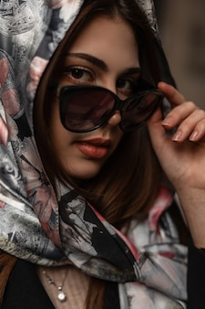 Ritratto alla moda abbastanza giovane donna con labbra sexy in sciarpa di seta elegante alla moda sulla testa. la ragazza moderna raddrizza gli occhiali da sole alla moda e guarda la telecamera. bella signora. volto femminile in primo piano
