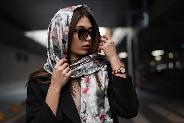Elegante ritratto giovane donna europea con belle labbra sexy in occhiali da sole alla moda in cappotto con elegante sciarpa di seta sulla testa in città. modello di moda ragazza moderna di affari. moda retrò. signora di bellezza.