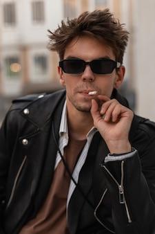 Ritratto alla moda di un giovane uomo in occhiali da sole alla moda in una giacca nera in pelle vintage in stile americano con una sigaretta vicino al muro sulla strada. brutale hipster si diverte a fumare all'aperto.
