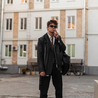 Elegante ritratto di un giovane uomo con sigaretta in occhiali da sole alla moda in giacca di pelle nera fresca con uno zaino alla moda su una strada cittadina. ragazzo hipster urbano in abbigliamento in stile americano fuma all'aperto