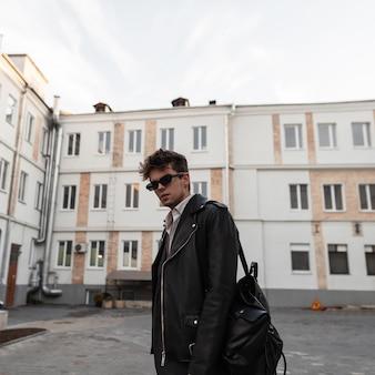 Elegante ritratto di un giovane uomo con un'acconciatura in occhiali da sole alla moda in una giacca di pelle nera fresca con uno zaino alla moda su una strada cittadina. ragazzo hipster urbano in abbigliamento giovanile in stile americano all'aperto