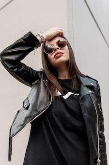 Elegante ritratto di una giovane donna swag con occhiali da sole alla moda alla moda in un'elegante giacca di pelle e felpa nera vicino a un muro grigio per strada. outfit look rock alla moda femminile urbano