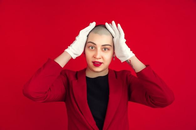 Posa alla moda. ritratto di giovane donna calva caucasica isolata sulla parete rossa. bellissimo modello femminile in giacca. emozioni umane, espressione facciale, vendite, concetto di annuncio. cultura pazzesca.