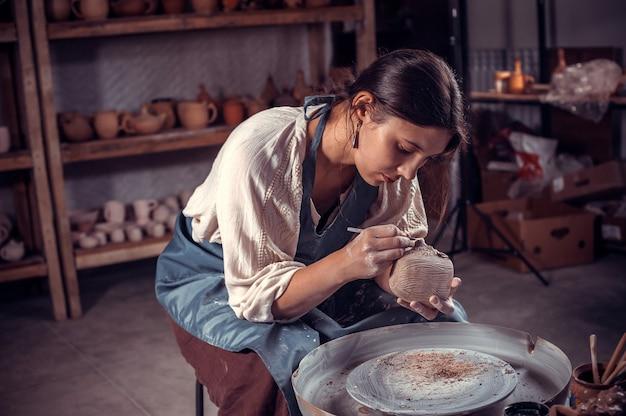 Lo scultore alla moda della donna della ceramica lavora con l'argilla