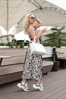 Elegante modello abbastanza alla moda donna con occhiali da sole con una borsa bianca in un abito vintage con un motivo in scarpe di moda in posa sulla strada